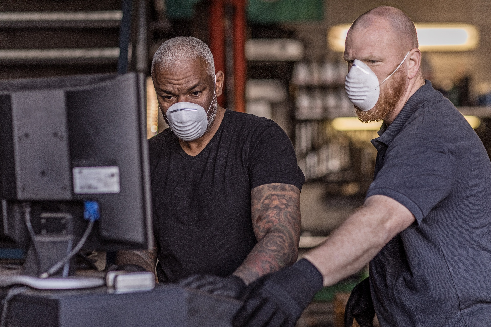 Two essential employees wearing masks at work
