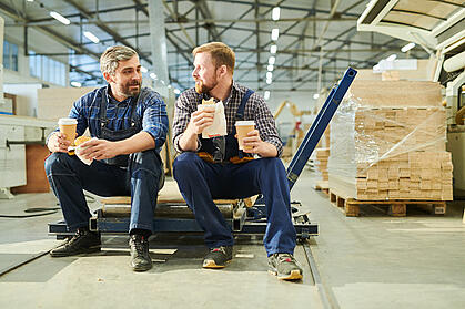 Two male employees on a break in warehouse eating lunch