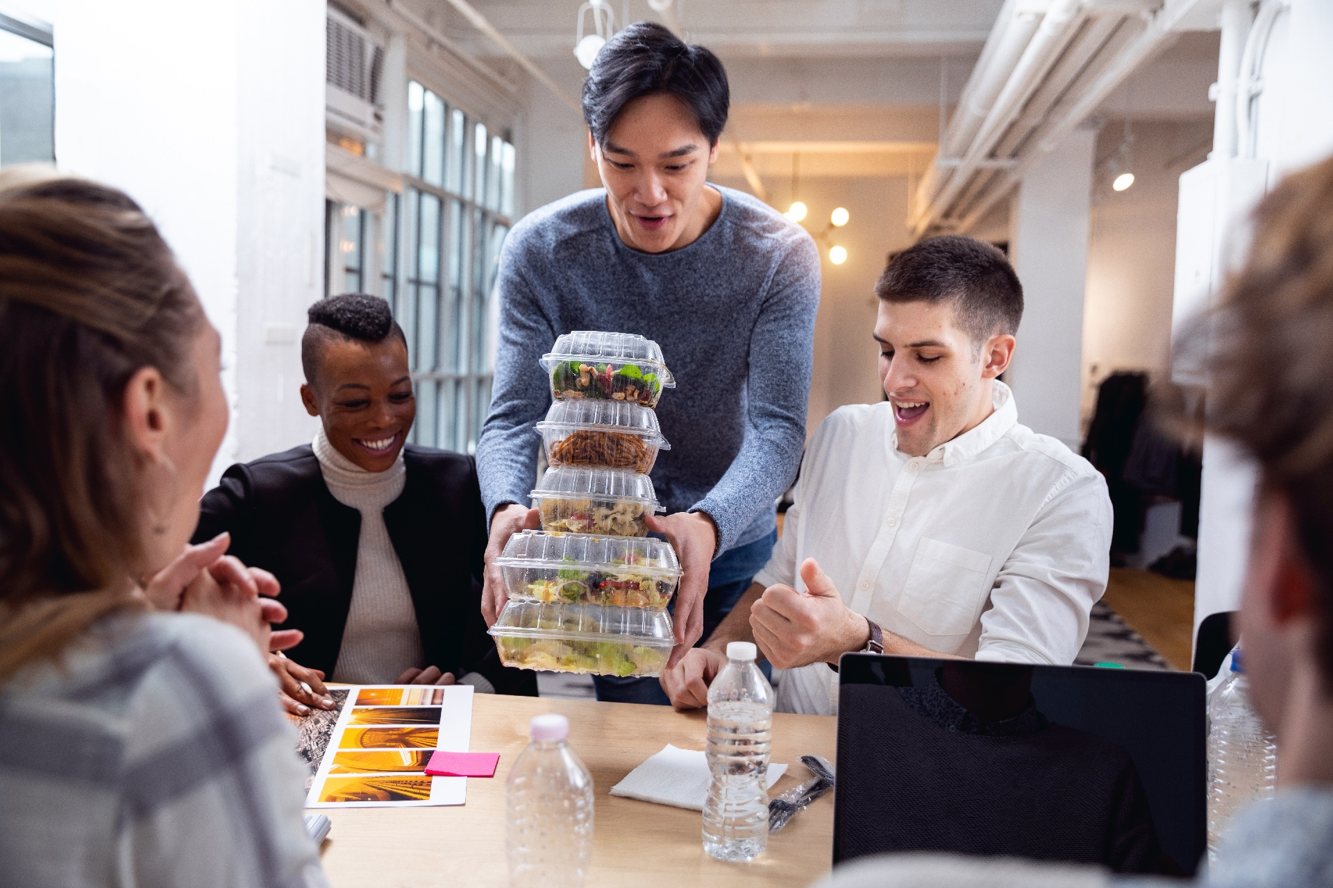 Coworkers at a group table being presented with lunch in clear containers