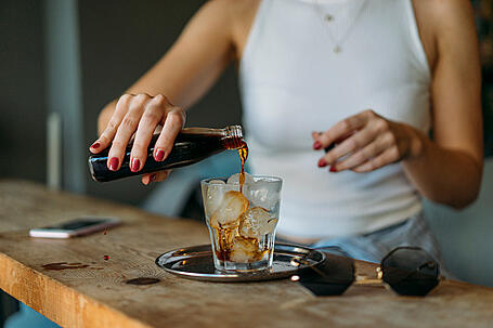 Cold Coffee Being Poured by a Woman into a Glass with Ice